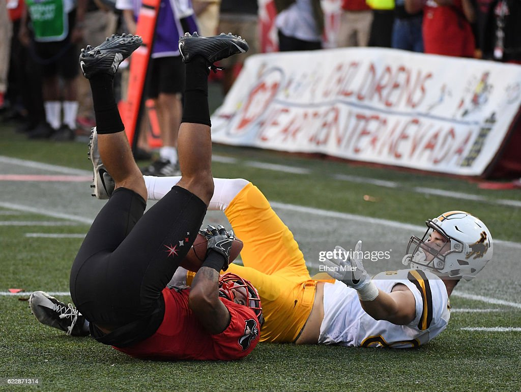 Defensive back Torry McTyer #4 of the UNLV Rebels intercepts the ball in the third overtime against wide receiver Jake Maulhardt #83 of the Wyoming Cowboys during their game at Sam Boyd Stadium on November 12, 2016 in Las Vegas, Nevada. UNLV won 69-66 in triple overtime.