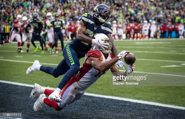 Defensive back Tre Flowers of the Seattle Seahawks defends a pass in the end zone intended for wide receiver Larry Fitzgerald of the Arizona...