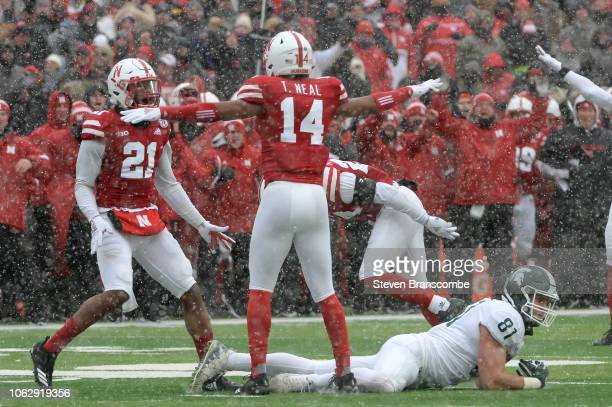 Defensive back Tre Neal of the Nebraska Cornhuskers and defensive back Lamar Jackson celebrates a late game fourth down stop as tight end Matt Sokol...