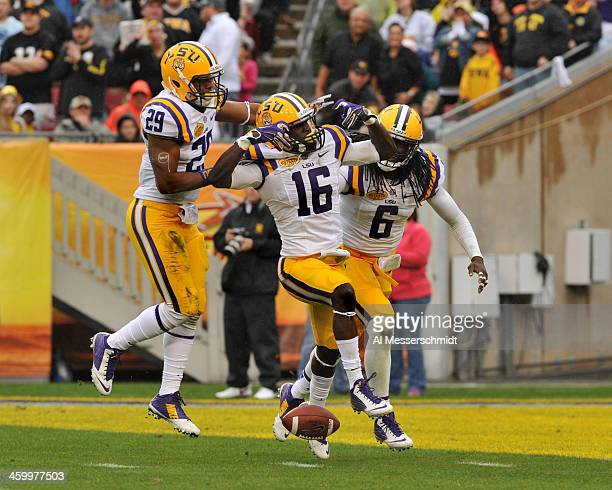 Defensive back Tre'Davious White of the LSU Tigers celebrates with Craig Loston and Rickey Jefferson after intercepting a first half pass against the...