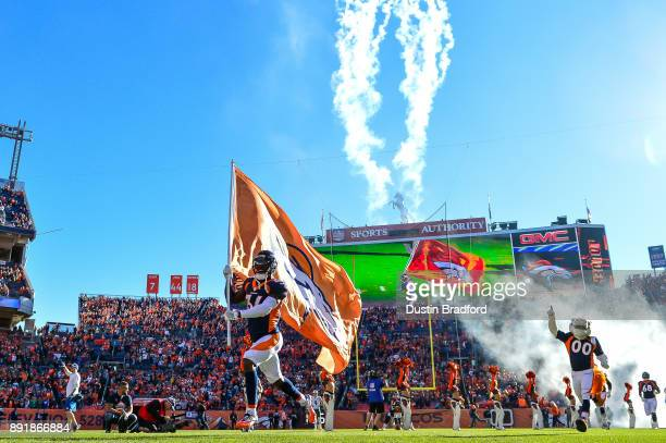 Defensive back Will Parks of the Denver Broncos carries a flag onto the field ahead of teammates before a game against the New York Jets at Sports...