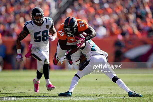 Defensive back Winston Guy of the Jacksonville Jaguars upends running back Montee Ball of the Denver Broncos as defensive end Jason Babin of the...