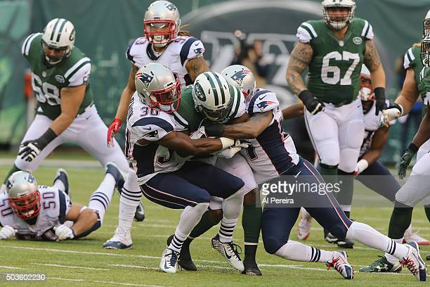 Defensive Backs Duron Harmon and Tavon Wilson of the New England Patriots makes a stop against the New York Jets at MetLife Stadium on December 27...