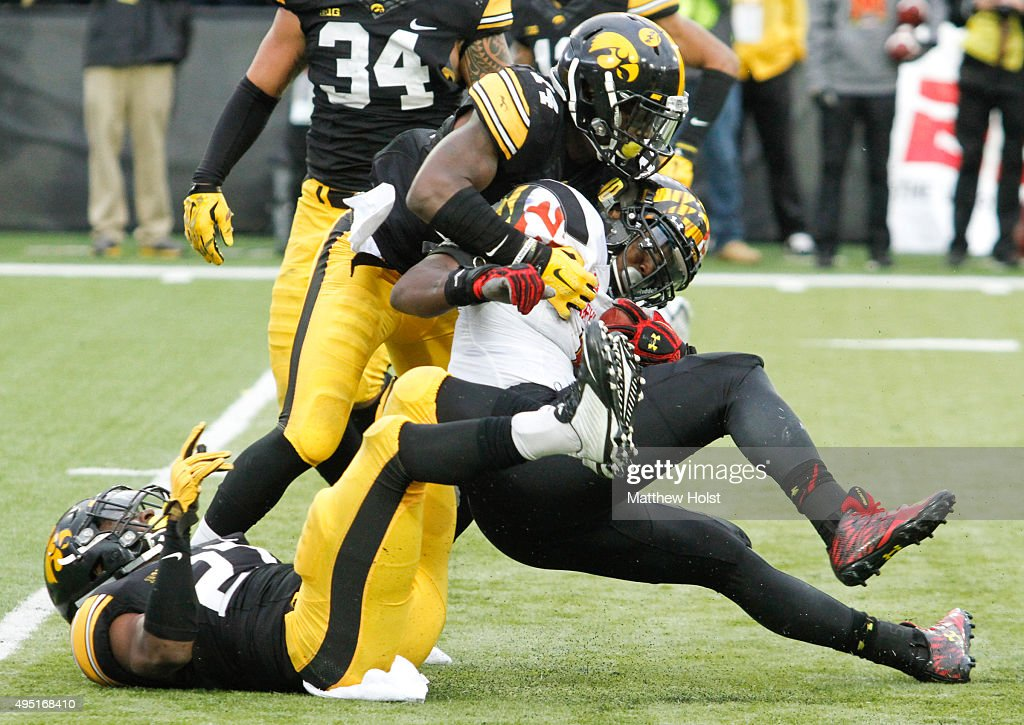 Defensive backs Jordan Lomax #27 and Desmond King #14 of the Iowa Hawkeyes combine to tackle running back Wes Brown #5 of Maryland Terrapins in the second half on October 31, 2015 at Kinnick Stadium, in Iowa City, Iowa.