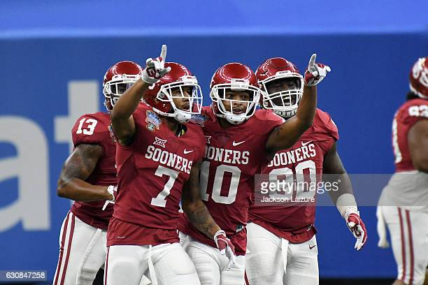 Defensive backs Jordan Thomas and Steven Parker celebrate with defensive lineman Neville Gallimore of the Oklahoma Sooners after Thomas' second half...