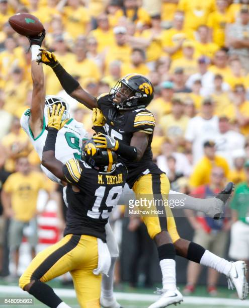 Defensive backs Josh Jackson and Miles Taylor of the Iowa Hawkeyes break up a pass intended for wide receiver Jalen Guyton of the North Texas Mean...