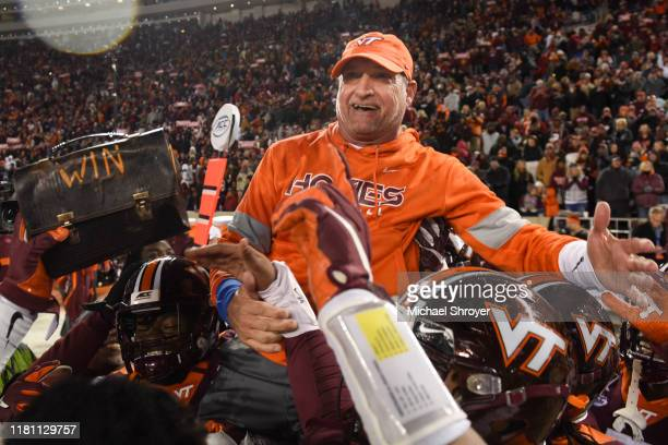 Defensive coordinator and associate head coach Bud Foster of the Virginia Tech Hokies is lifted into the air following the victory against the Wake...