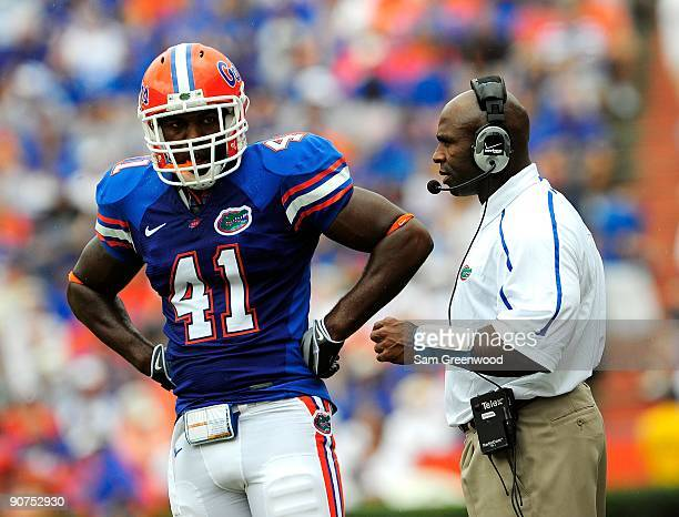 Defensive coordinator Charlie Strong of the Florida Gators talks with Ryan Stamper during the game against the Troy Trojans at Ben Hill Griffin...
