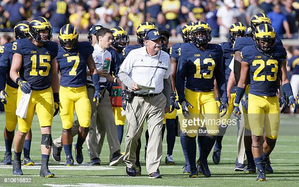 Defensive coordinator Don Brown leads some Michigan players down the field before a game against the Colorado Buffaloes at Michigan Stadium on...