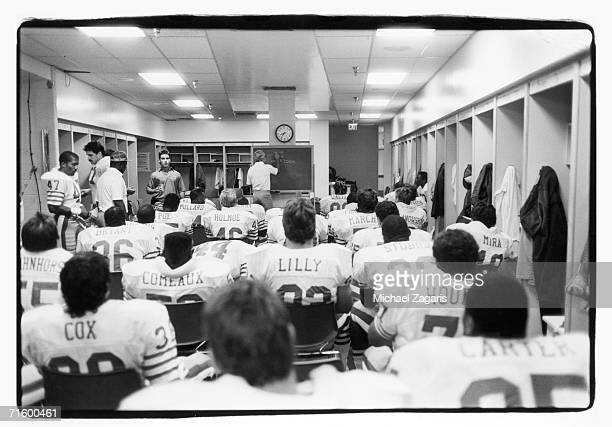 Defensive coordinator George Seifert of the San Francisco 49ers writes on the chalkboard as players look on at halftime of the preseason game against...
