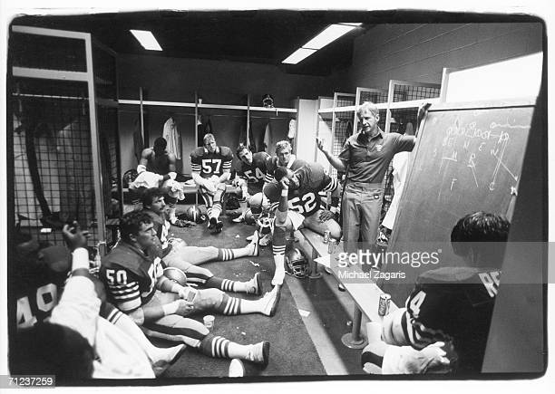 Defensive coordinator George Seifert of the San Francisco 49ers talks to his players in the locker room at halftime of the game against the Houston...