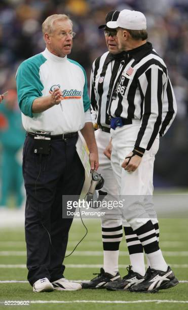 Defensive Coordinator Jim Bates of the Miami Dolphins talks to referee Bernie Kukar during NFL action against the Baltimore Ravens at MT Bank Stadium...