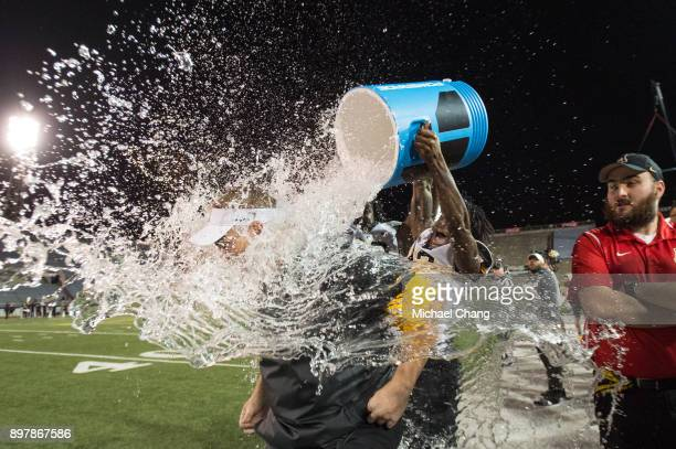 Defensive coordinator Nate Woody of the Appalachian State Mountaineers gets dunked with water after defeating the Toledo Rockets on December 23 2017...