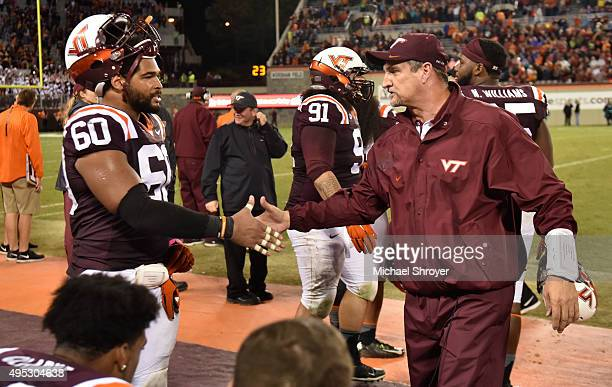 Defensive coordinator of the Virginia Tech Hokies Bud Foster congratulates defensive tackle Woody Baron of the Virginia Tech Hokies during the...
