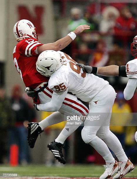Defensive end Aaron Lewis of the Texas Longhorns drills quarterback Zac Taylor of the Nebraska Cornhuskers as he throws the ball in the third quarter...