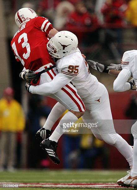 Defensive end Aaron Lewis of the Texas Longhorns hits quarterback Zac Taylor of the Nebraska Cornhuskers as he throws the ball in the third quarter...