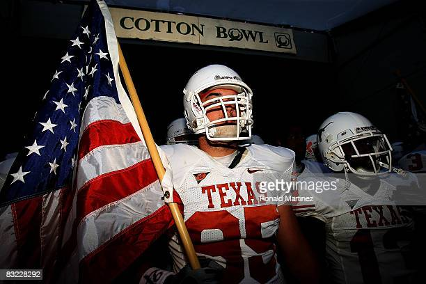 Defensive end Aaron Lewis the Texas Longhorns carries a flag as he enters the field before their Red River Rivalry game against the Oklahoma Sooners...