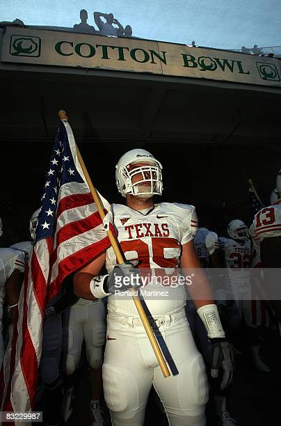 Defensive end Aaron Lewis the Texas Longhorns carries a flag as he enters the field before the Red River Rivalry game against the Oklahoma Sooners at...