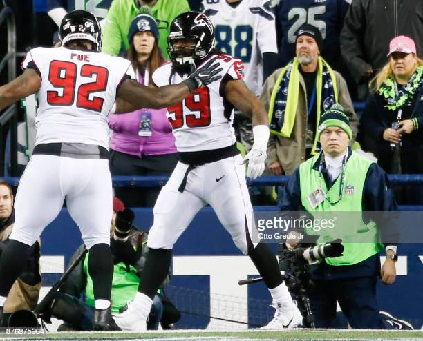 Defensive end Adrian Clayborn and Dontari Poe of the Atlanta Falcons celebrate Clayborn's fumble recovery for a touchdown off of quarterback Russell...
