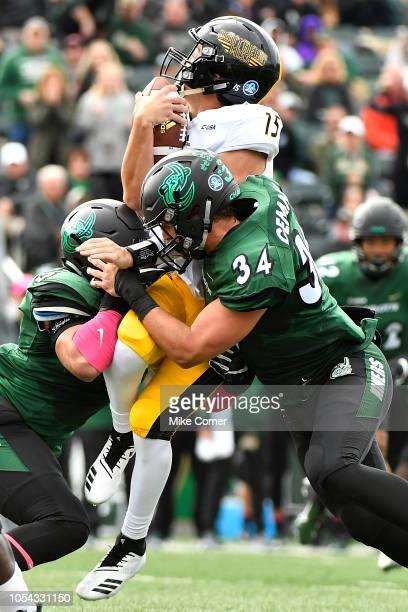 Defensive end Alex Highsmith and linebacker Jeff Gemmell of the Charlotte 49ers tackle quarterback Jack Abraham of the Southern Miss Golden Eagles...