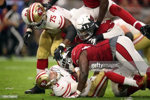Defensive end Benson Mayowa and defensive end Markus Golden of the Arizona Cardinals tackle quarterback CJ Beathard of the San Francisco 49ers during...