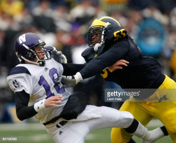 Defensive end Brandon Graham of the Michigan Wolverines knocks down quarterback C J Bacher of the Northwestern Wildcats in the fourth quarter on...