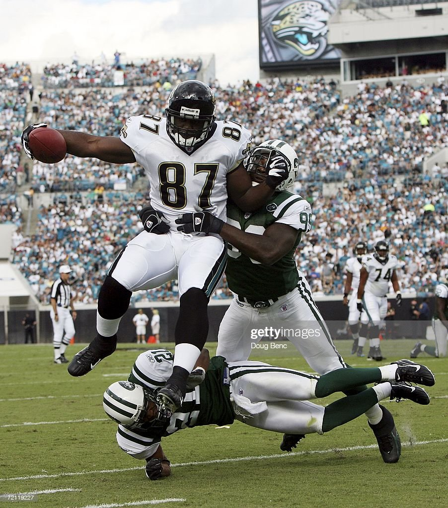Defensive end Bryan Thomas #99 and cornerback Andre Dyson #21 of the New York Jets try to bring down tight end George Wrighster #87 of the Jacksonville Jaguars at Alltel Stadium on October 8, 2006 in Jacksonville, Florida. The Jaguars defeated the Jets 41-0.