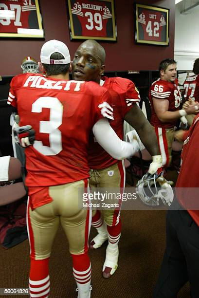 Defensive end Bryant Young and quarterback Cody Pickett of the San Francisco 49ers celebrate in the locker room after the NFL game against the Tampa...