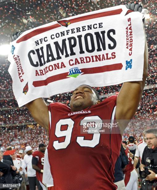 Defensive end Calais Campbell of the Arizona Cardinals celebrates after the game by holding up a championship towel after the victory against the...