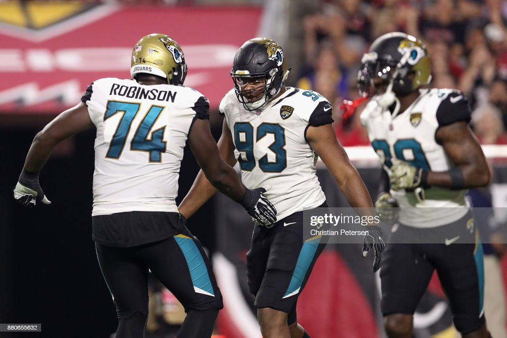 Defensive end Calais Campbell #93 of the Jacksonville Jaguars celebrates with offensive tackle Cam Robinson #74 after scoring a touchdown against the Arizona Cardinals during the second half of the NFL game at the University of Phoenix Stadium on November 26, 2017 in Glendale, Arizona. The Cardinals defeated the Jaguars 27-24.