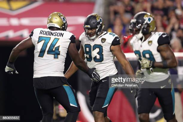 Defensive end Calais Campbell of the Jacksonville Jaguars celebrates with offensive tackle Cam Robinson after scoring a touchdown against the Arizona...