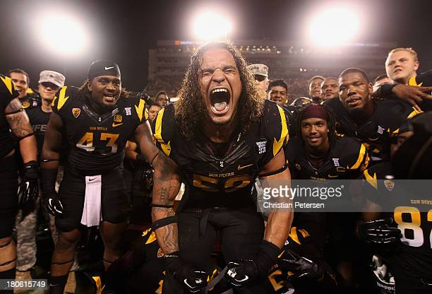 Defensive end Carl Bradford of the Arizona State Sun Devils celebrates alongside teammates after defeating the Wisconsin Badgers 3230 in the college...