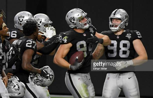 Defensive end Carl Nassib of the Las Vegas Raiders celebrates with teammates, including defensive end Maxx Crosby, after Nassib intercepted a Denver...