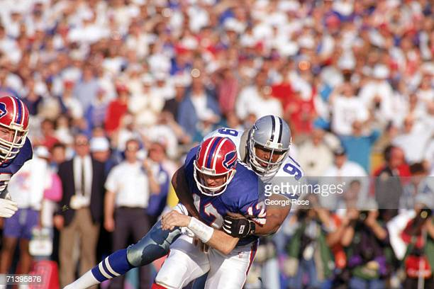 Defensive end Charles Haley of the Dallas Cowboys puts a hit on quarterback Jim Kelly of the Buffalo Bills during Super Bowl XXVII at the Rose Bowl...