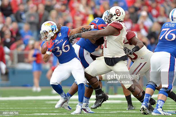 Defensive end Charles Tapper of the Oklahoma Sooners tries to tackle running back Taylor Cox of the Kansas Jayhawks during the Sooners victory on...