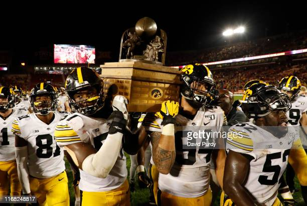 Defensive end Chauncey Golston, left, and defensive end A.J. Epenesa of the Iowa Hawkeyes carry the Iowa Corn Cy-Hawk Trophy off the field after...