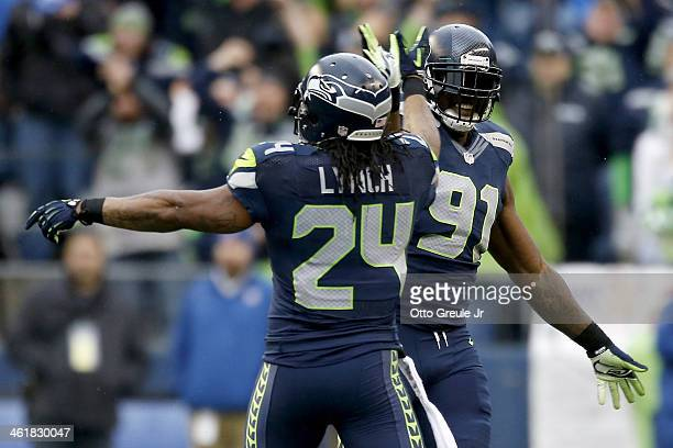 Defensive end Chris Clemons of the Seattle Seahawks celebrates with running back Marshawn Lynch after the Seahawks recover a fumble in the second...