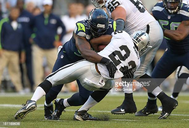 Defensive end Chris Clemons of the Seattle Seahawks tackles Taiwan Jones of the Oakland Raiders at CenturyLink Field on August 30 2012 in Seattle...