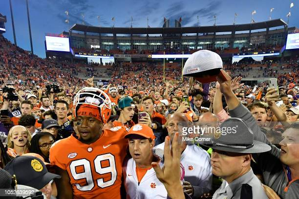 Defensive end Clelin Ferrell and head coach Dabo Swinney of the Clemson Tigers embrace at midfield while surrounded by fans singing the Clemson Alma...