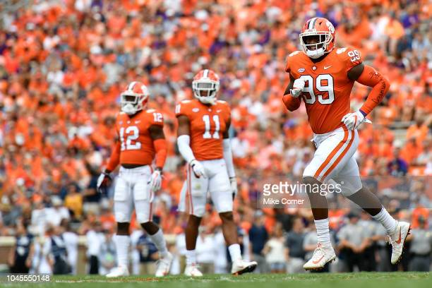 Defensive end Clelin Ferrell runs to the sideline as defensive back K'Von Wallace and safety Isaiah Simmons of the Clemson Tigers look on during the...