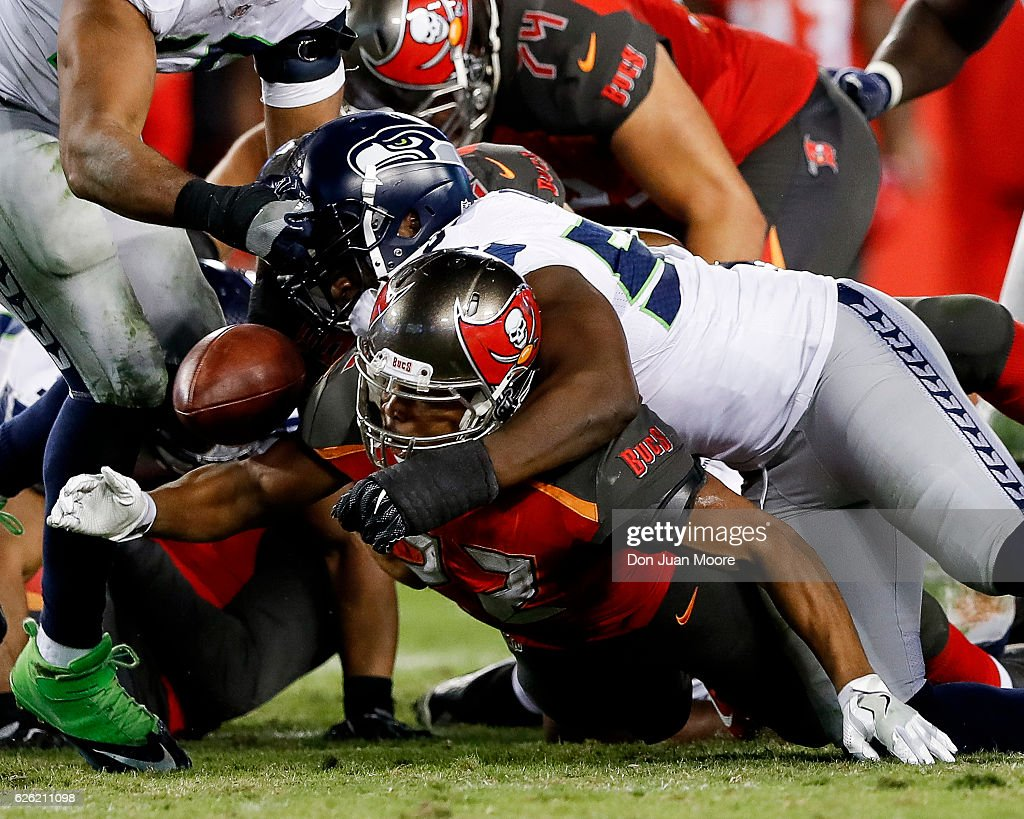 Defensive End Cliff Avril #56 of the Seattle Seahawks strips the ball loose from Running back Doug Martin #22 of the Tampa Bay Buccaneers during the game at Raymond James Stadium on November 27, 2016 in Tampa, Florida. The Bucs defeated the Seahawks 14 to 5.