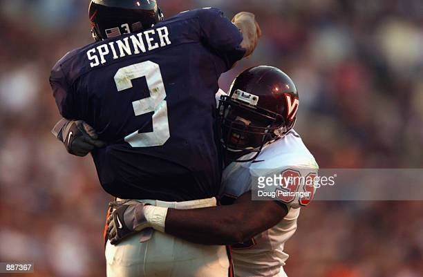 Defensive end Cols Colas of the Virginia Tech Hokies hits quarterback Bryson Spinner of the University of Virginia Cavaliers during the NCAA football...