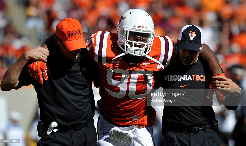 Defensive end Dadi Nicolas #90 of the Virginia Tech Hokies is helped off the field after an injury against the Western Michigan Broncos in the second half at Lane Stadium on September 27, 2014 in Blacksburg, Virginia. Virginia Tech defeated Western Michigan 35-17.