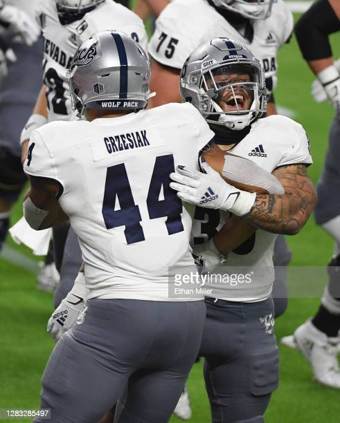 Defensive end Daniel Grzesiak and running back Toa Taua of the Nevada Wolf Pack celebrate after Taua ran for a 4-yard touchdown against the UNLV...