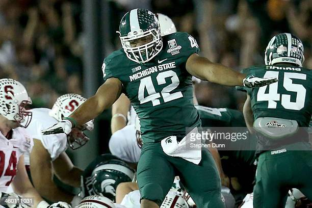 Defensive end Denzel Drone of the Michigan State Spartans celebrates stopping the Stanford Cardinal on fourth down to take possesion in the final...