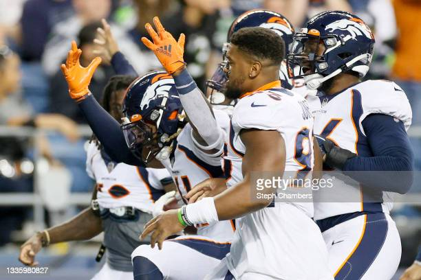 Defensive end DeShawn Williams of the Denver Broncos reacts with his teammates after intercepting the ball in the first half during an NFL preseason...