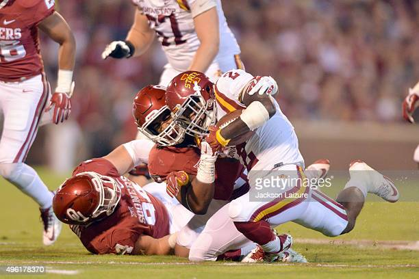 Defensive end Devante Bond and defensive tackle Matt Dimon of the Oklahoma Sooners tackle running back Mike Warren of the Iowa State Cyclones during...