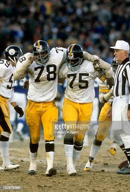 Defensive End Dwight White of the Pittsburgh Steelers is being help off the field by teammate Joe Greene December 19 1976 during an NFL football game...