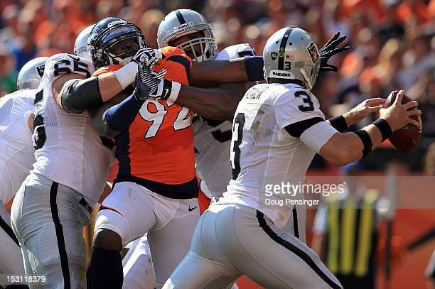 Defensive end Elvis Dumervil of the Denver Broncos is blocked by guard Mike Brisiel of the Oakland Raiders and tackle Khalif Barnes of the Oakland...