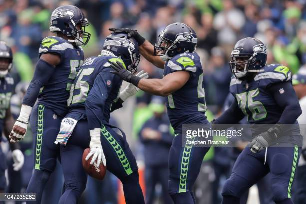 Defensive End Frank Clark of the Seattle Seahawks celebrates with his teammates after his interception in the first quarter against the Los Angeles...